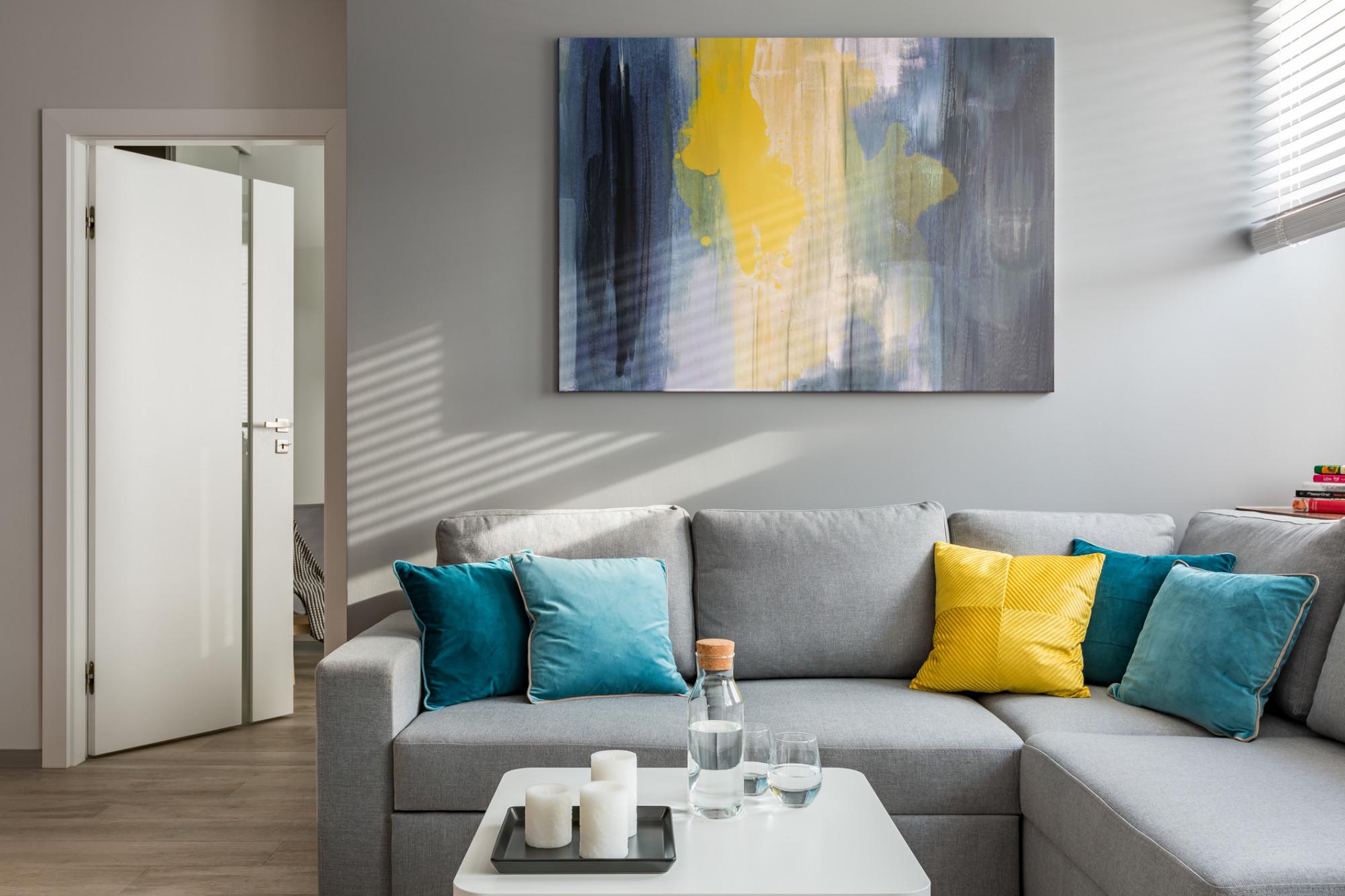 Sivá sedačka so žltým a modrými vankúšmi a farebne zladený obraz