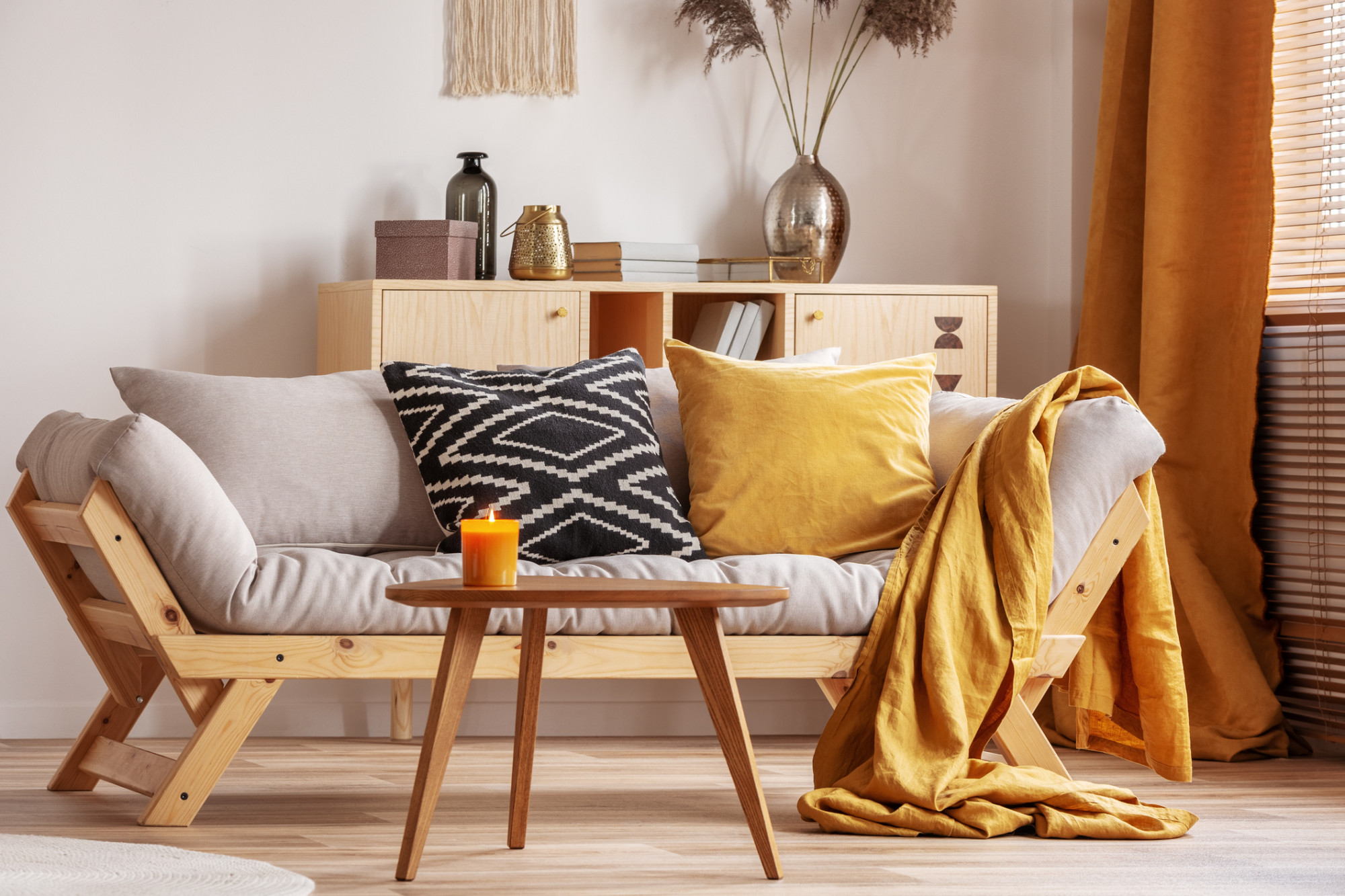 Svetlá pohovka so žltými textíliami a drevený nábytok