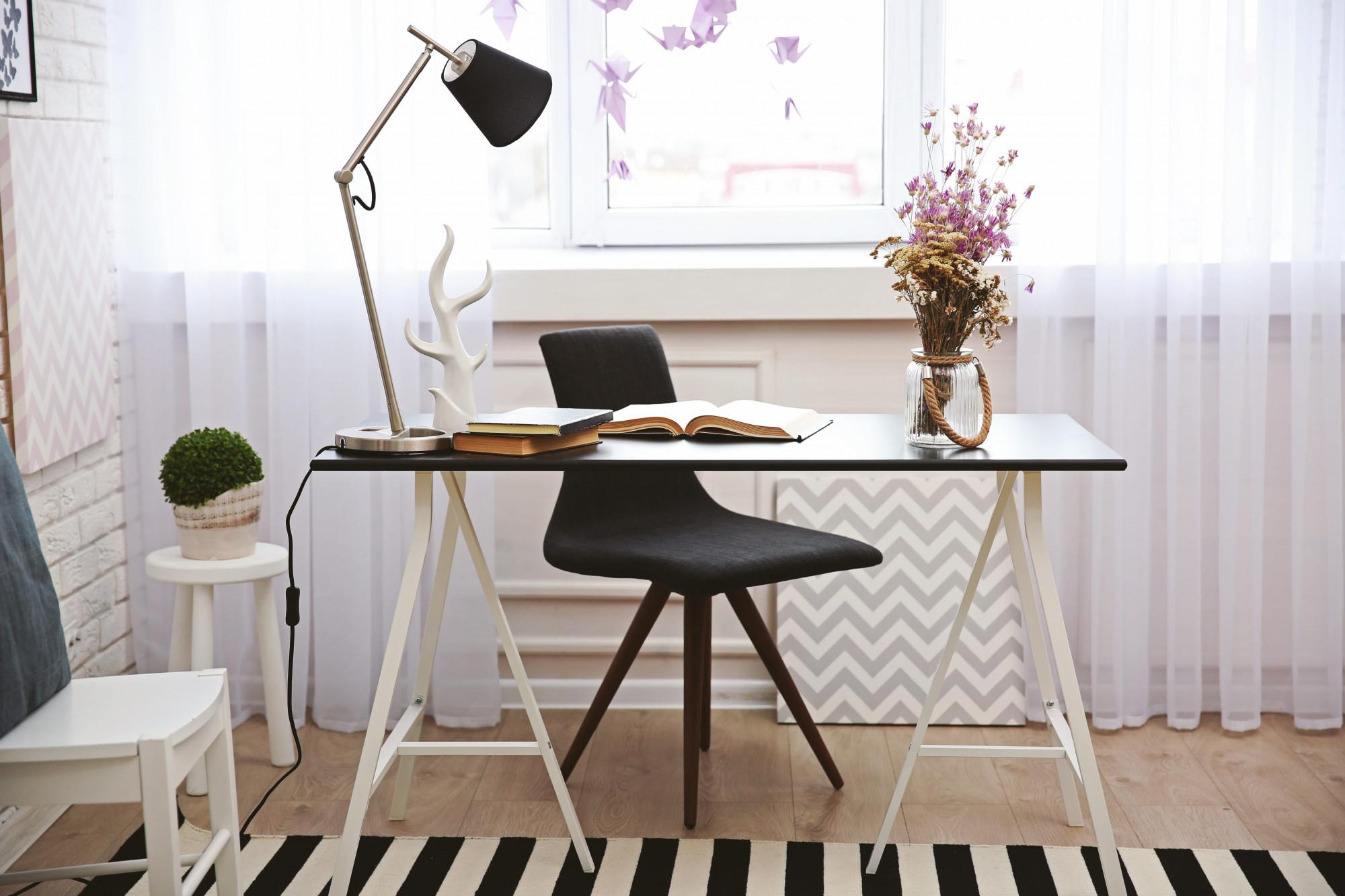 Čierno-biely písací stôl, stolová lampa a čierna stolička