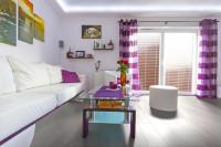 Biela obývacia izba ladená fialovými doplnkami