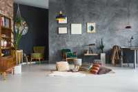 Sivá stena s menšími obrazmi, retro kreslá, závesné lampy