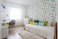 Posteľ v detskej izbe s vankúšmi zladenými s tapetou