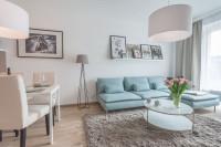 Svetlomodrá rohová sedačka v obývačke s jedálenským stolom