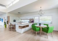 Svieže zelené jedálenské stoličky v priestrannej bielej kuchyni