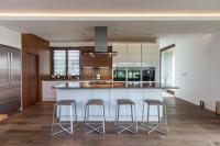 Priestranná moderná kuchyňa v kombinácii bielej a hnedej