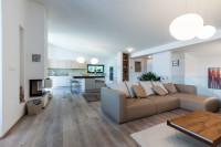 Béžová rohová sedačka v priestannej obývačke s kuchyňou