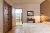 Veľká manželská posteľ a prírodné doplnky vo svetlej spálni