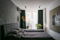Sivá čalúnená manželská posteľ v elegantnej minimalistickej spálni