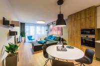Okrúhly jedálenský stôl a stoličky v modernej obývačke s kuchyňou