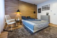 Minimalistická manželská posteľ a hojdacie kreslo v modernej spálni