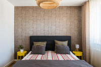 Manželská posteľ v útulnej spálni s kontrastnou tapetou