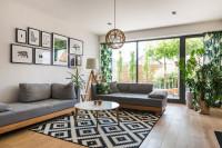 Sivé pohovky a okrúhly konferenčný stolík v modernej obývačke
