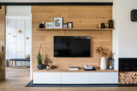 Biely minimalistický stolík pod TV v kontraste s drevenou stenou