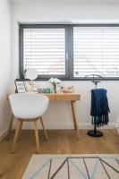 Drevený toaletný stolík a biela plastová stolička