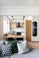 Drevený stôl a čierne stoličky v industriálnej kuchyni