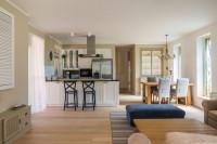 Čierne barové stoličky a jedálenský kút v priestrannej obývačke s kuchyňou
