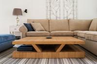 Drevený konferenčný stolík a béžová pohovka vo svetlej obývačke