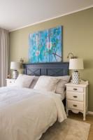 Drevená manželská posteľ a biele nočné stolíky v útulnej spálni