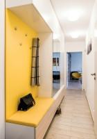 Úzka svetlá predsieň so žltým vešiakovým panelom
