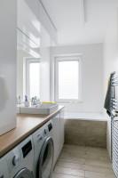 Úzka kúpeľňa v kombinácii bielej a prírodných tónov