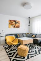 Rohová sedačka a žlté kreslo v škandinávskej obývačke