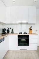 Moderná biela kuchynská linka v kombinácii so svetlým drevom