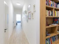 Drevená knižnica a dekorácia z fotorámikov v úzkej chodbe
