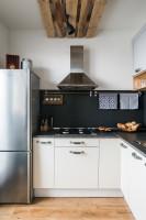 Biela kuchynská linka v kontraste s čiernou zástenou