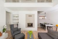Sivé látkové kreslo vo svetlej obývačke s kuchyňou