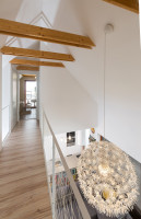 Galéria na poschodí domu s elegantným bielym svietidlom