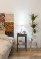 Manželská posteľ s čalúneným čelom a drevený nočný stolík