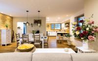 Jedálenský stôl a drevené stoličky v priestrannej obývačke s kuchyňou