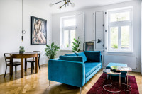 Modrá pohovka s podnožkou a dvojicou okrúhlych stolíkov