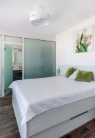 Manželská posteľ v bielych tónoch a sklenená stena do kúpeľne