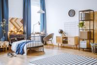 Kovová posteľ, čierno-biely koberec, drevená skrinka a modré závesy