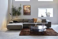 Obývacia izba s rohovou sedačkou a preskleným okrúhlym konferenčným stolíkom