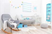 Sivé hojdacie kreslo, biela posteľ a sivé a modré doplnky