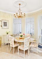 Oválny biely drevený stôl so stoličkami s kvetinovým vzorom