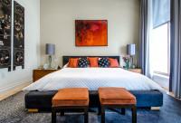 Manželská posteľ s nočnými stolíkmi po stranách a dvoma taburetkami