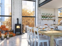 Dlhý drevený jedálenský stôl a biele stoličky vo vzdušnej škandinávskej kuchyni