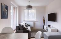 Malá, jednoducho zariadená obývačka so sivou pohovkou