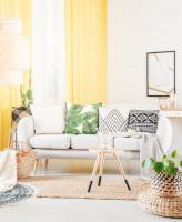 Obývačka s bielou pohovkou a žltými závesmi