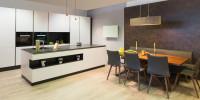 Moderná biela kuchynská linka a dlhý drevený jedálenský stôl so sivými stoličkami