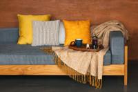 Sivá pohovka s dekoračnými vankúšmi a dekou v žltých tónoch