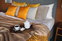 Čalúnená manželská posteľ a dekoračné vankúše v jesenných farbách