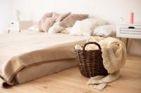 Priestranná posteľ a prútený kôš s pletenou dekou