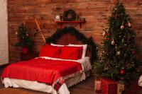 Manželská posteľ a vianočný stromček v rustikálnej spálni s červenými akcentami
