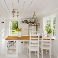 Dlhý jedálenský stôl a biele stoličky v provensálskej kuchyni