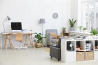 Písací stôl a sivé kreslo v modernej obývačke