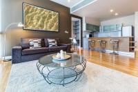 Sivá pohovka a okrúhly konferenčný stolík v modernej obývačke s kuchyňou